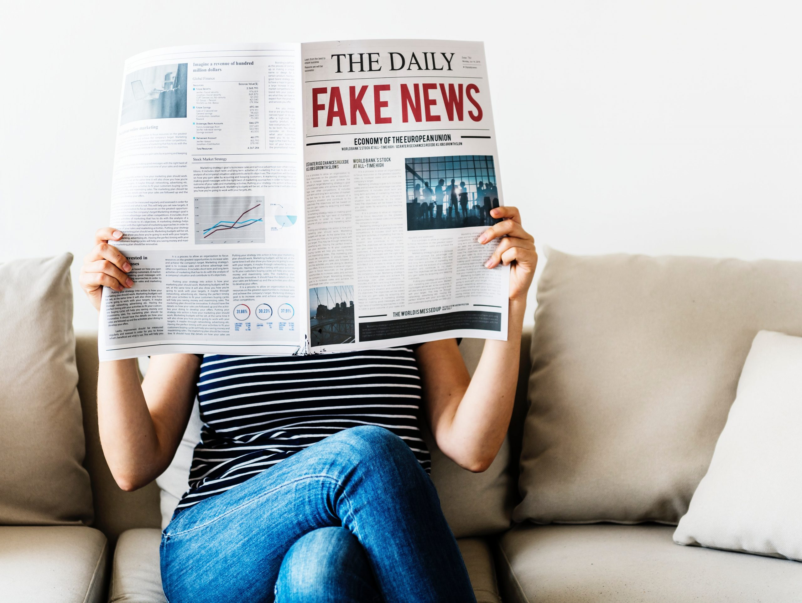 women reading a newspaper that states 'fake news' in re text