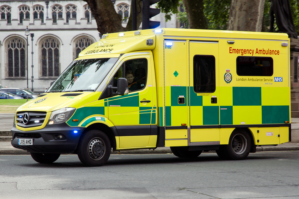 yellow and green london ambulance van driving to an emergency