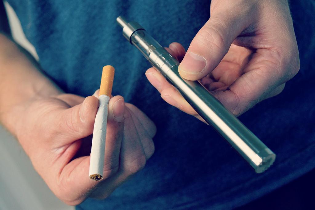 man holding a cigarette and a vape pen e-cigarette
