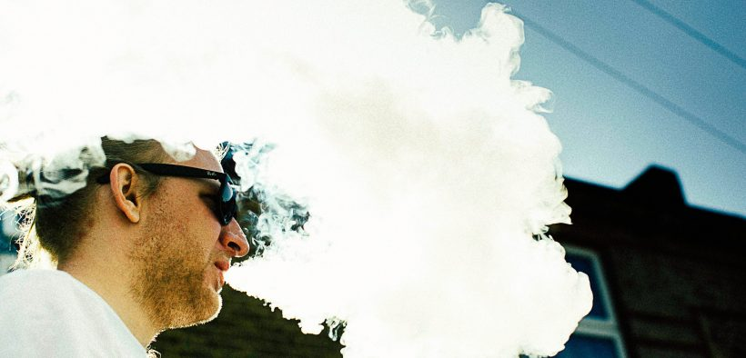 white man in sunglasses producing a cloud of vapour after using e-cigarette