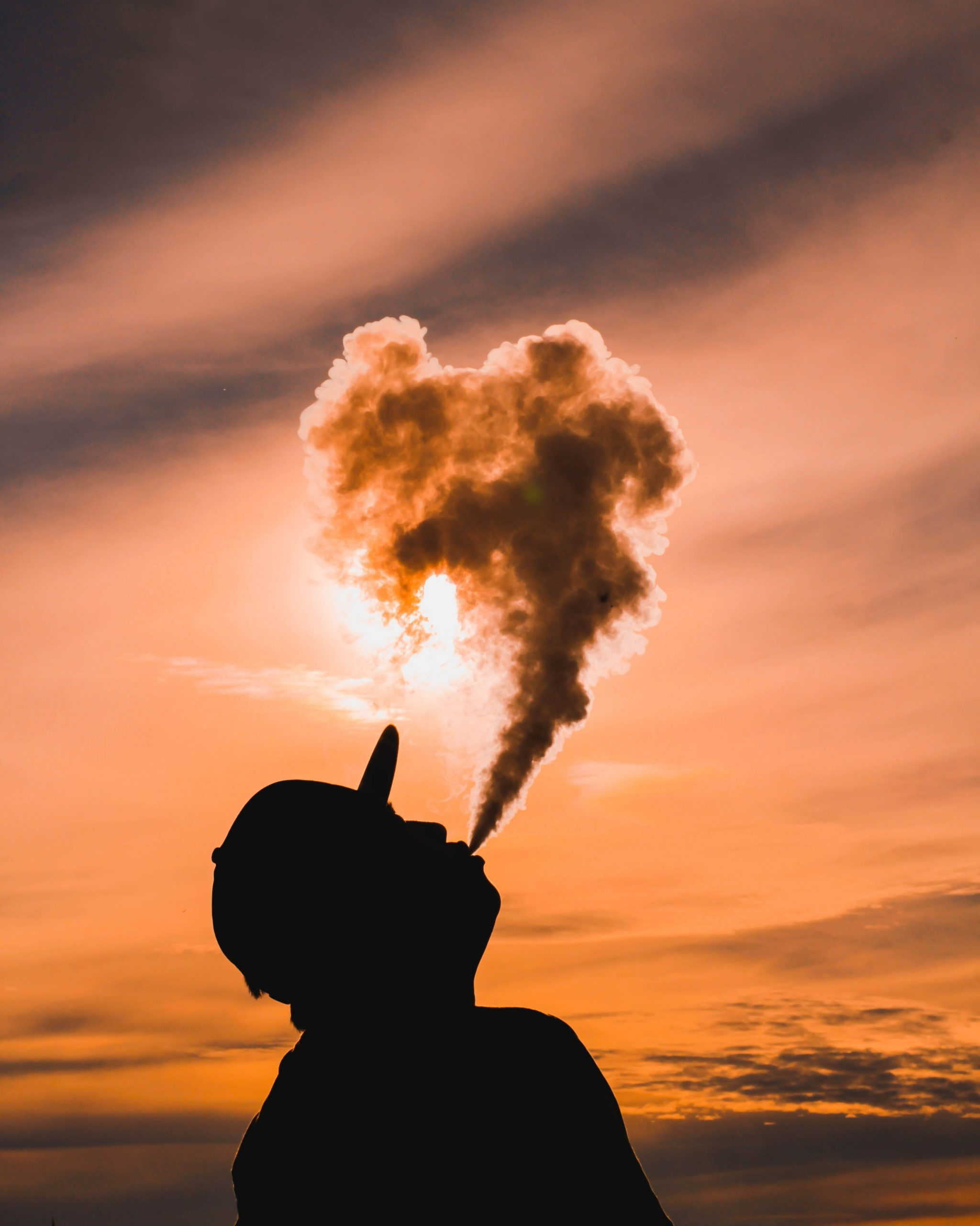 A person wearing a cap blows a vape into the air