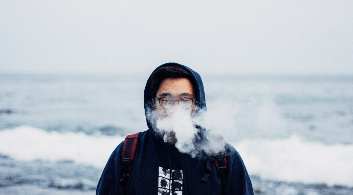 Man vaping by the sea