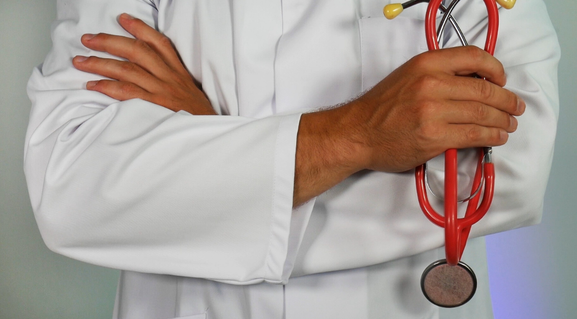 Doctor with folded arms holding a stethoscope