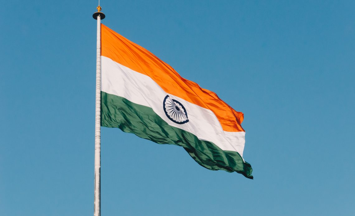 Indian flag flying in a breeze against a bright blue background