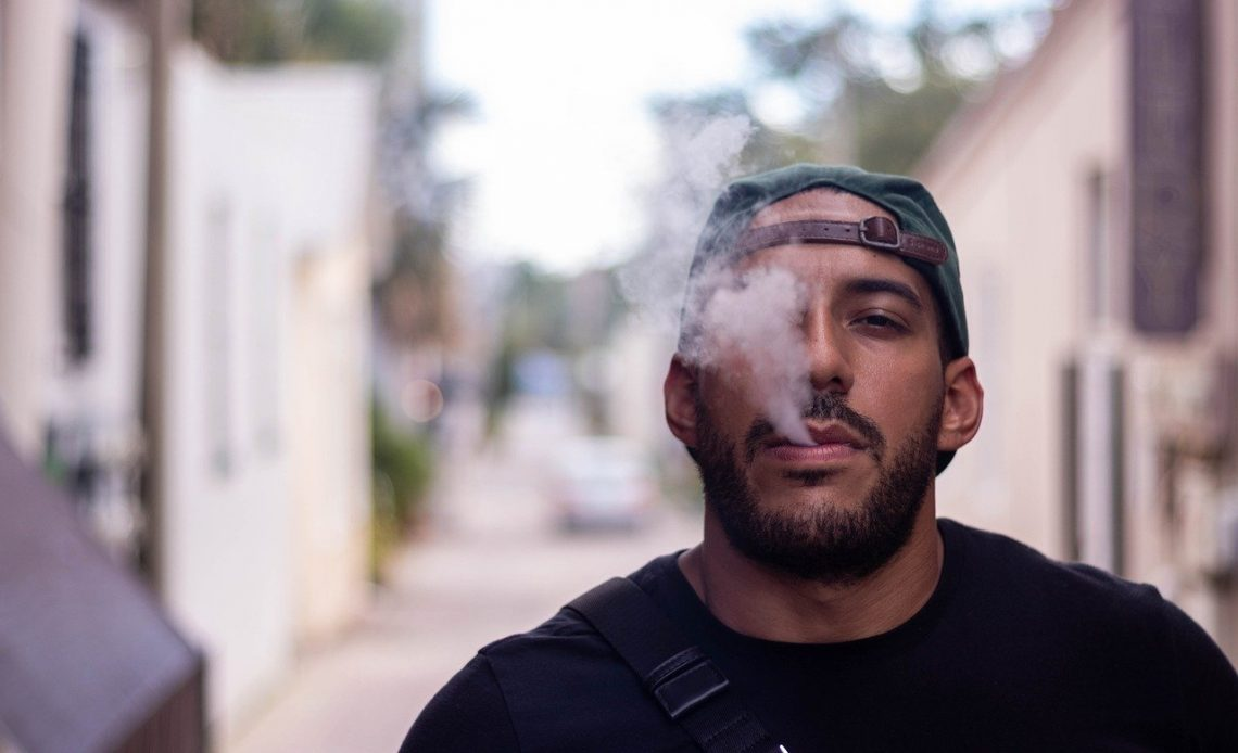 Man in cap vaping