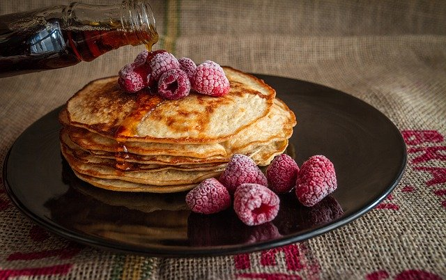 Pancakes drizzled in maple syrup topped with raspberries