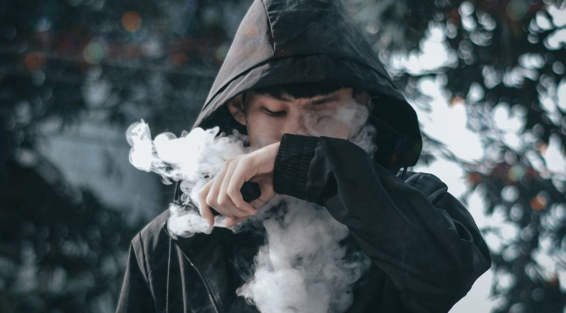A man with a vape in his hand