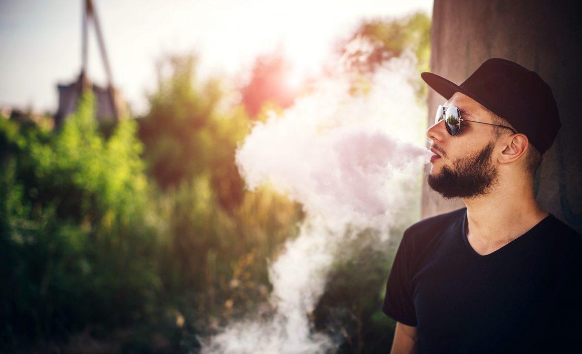 Man in sunglasses and cap vaping