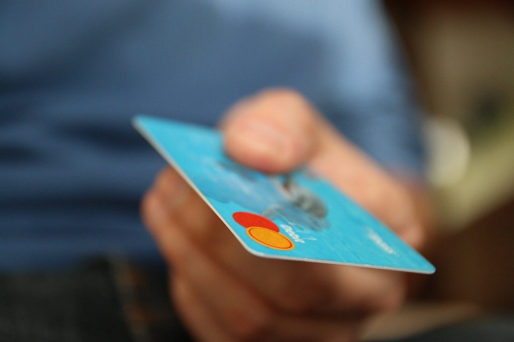 A man hands over a light blue credit card for a sale.