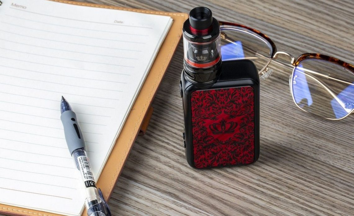 A red and black vape sits ona. wooden desk next to a notepad and a pair of glasses