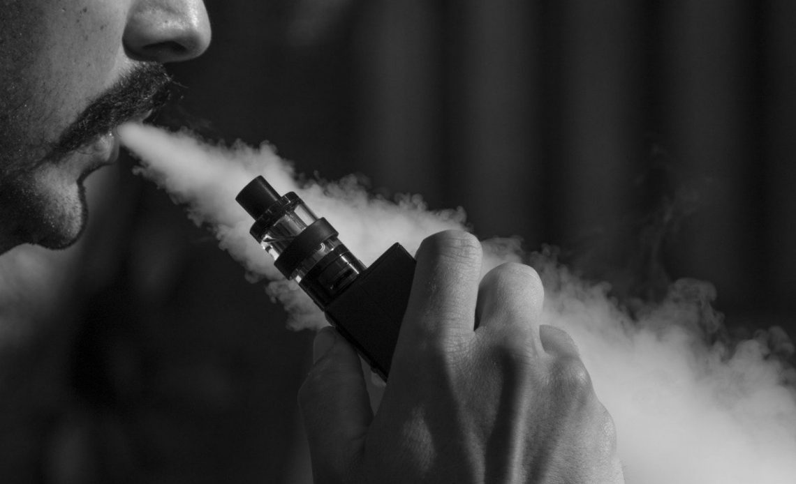 A black and white image of a man exhaling a vape device