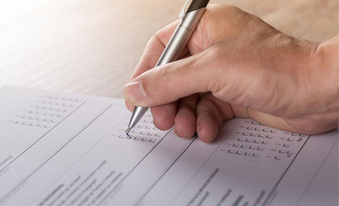 A white hand holding a pen to paper for a survey