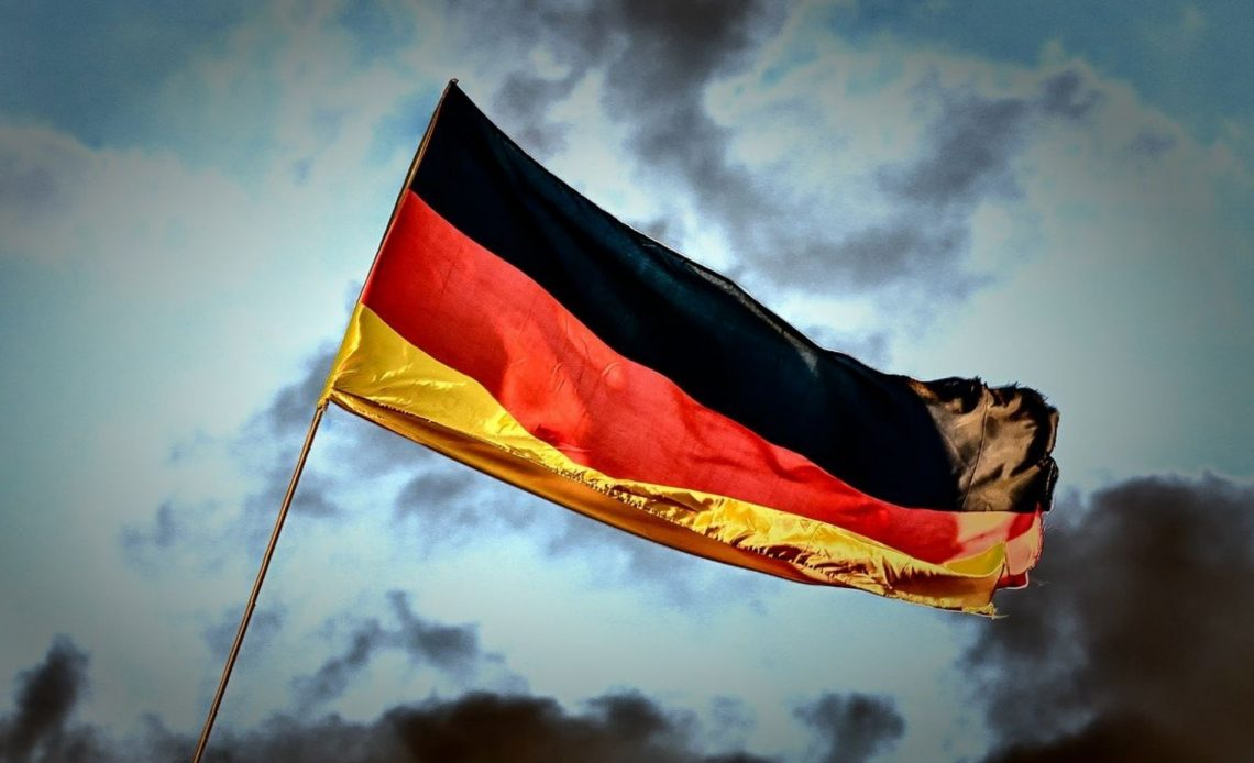 A German flag against a dark night sky and clouds