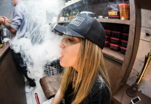 A woman with a baseball cap vapes a big cloud