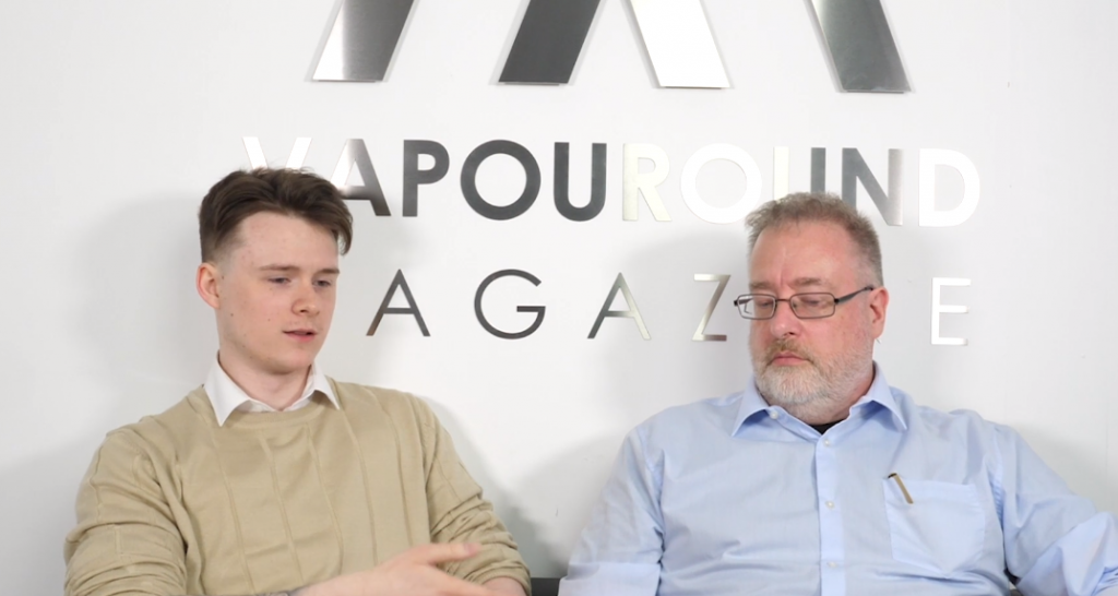 Two men sit beside each other. One is wearing a beige jumper and the other is in a blue shirt. They are in discussion in front of a sign that says Vapouround Magazine.