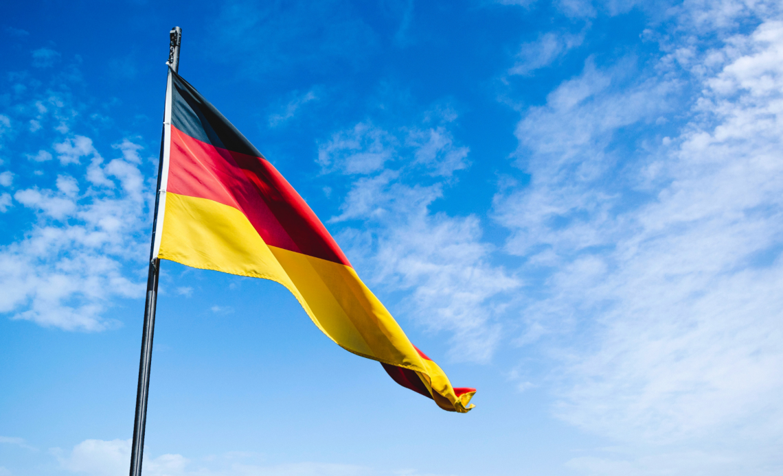 A German flag flying in a blue sky with white cloud