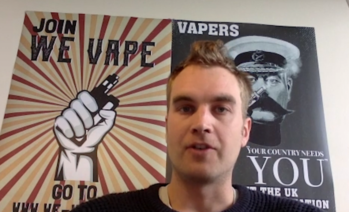 A man sits in front of a poster that says WE VAPE with a fist holding a vape device in it