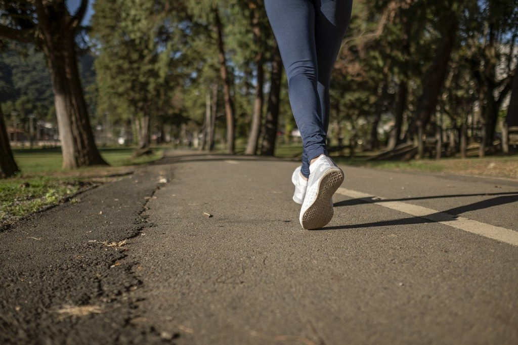 A countryside road with a person jogging in the middle wearing blue leggings and white sneakers